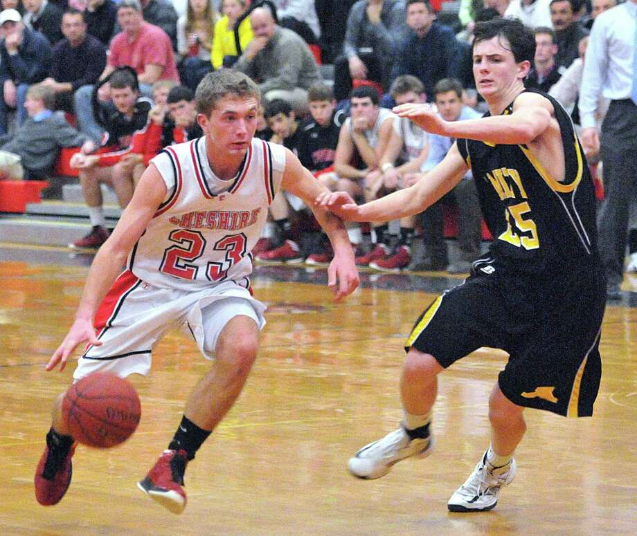 Cheshire's Eric Dietrich drives past Amity's Dave Ryan during the first half of last week's Cheshire win. Amity took a one-game lead over Cheshire this Friday after Amity beat Sheehan and Cheshire lost to Shelton. Peter Casolino/Register.