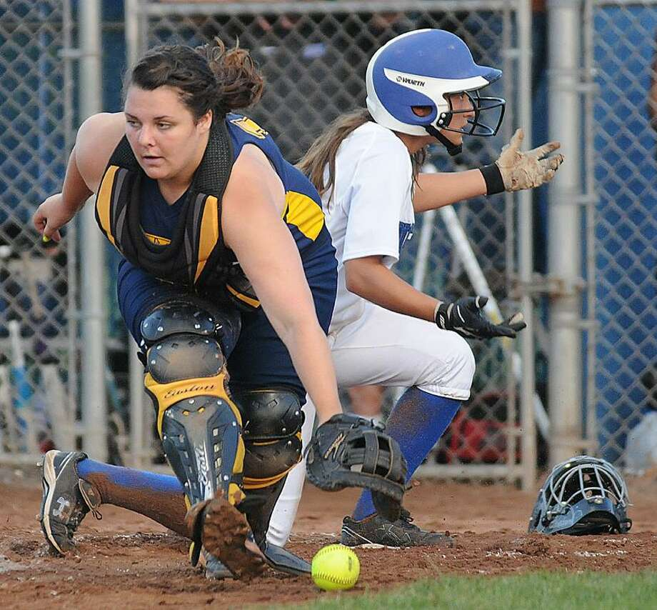 (Catherine Avalone/The Middletown Press) Mercy senior captain and catcher Tyler Keegan chases down a ball as Southington sophomore Lauren Zazzaro looks for the umpire's call at Frank Biondi Softball Field at West Haven High School Sunday night. Zazzaro scored the one and only run of the game in the Class LL State Championship winning 1-0.. / TheMiddletownPress