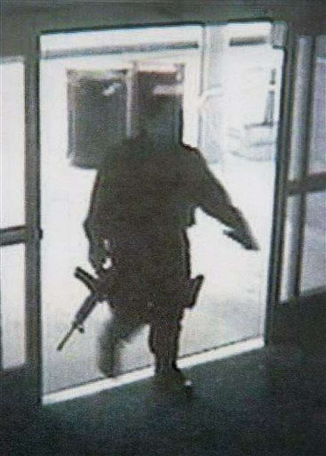 This photo provided by the Santa Monica Police Department during a news conference Saturday, June 8, 2013, shows a frame grab from a surveillance camera revealing the suspect entering Santa Monica College Friday, in Santa Monica, Calif. The Police chief said Saturday that the gunman who went on a chaotic rampage killing four people before being fatally shot by police at the college planned the attack and was capable of firing 1,300 rounds of ammunition. (AP Photo/Santa Monica Police Department) Photo: AP / FR170512 AP