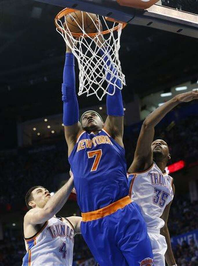 New York Knicks forward Carmelo Anthony (7) dunks between Oklahoma City Thunder forward Nick Collison (4) and forward Kevin Durant (35) in the second quarter of an NBA basketball game in Oklahoma City, Sunday, April 7, 2013. (AP Photo/Sue Ogrocki) Photo: ASSOCIATED PRESS / AP2013