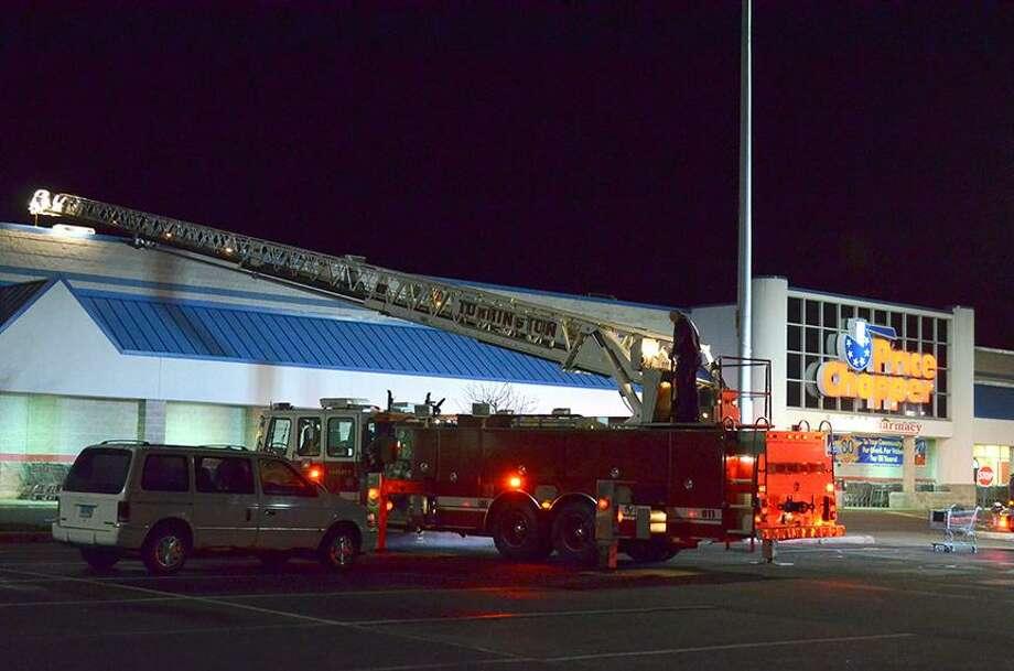 A ladder truck extends over the roof of Price Chopper in Torrington Sunday evening. Jason Siedzik / Register Citizen