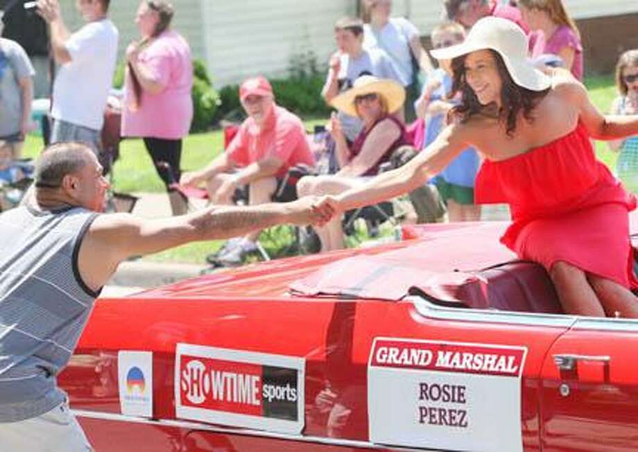 JOHN HAEGER @ONEIDAPHOTO ON TWITTER/ONEIDA DAILY DISPATCH Rosie Perez , grand garshal of the International Boxing Hall of Fame Parade of Champions shakes the hand of a fan during the parade in Canastota N.Y. on Sunday, June 9, 2013.