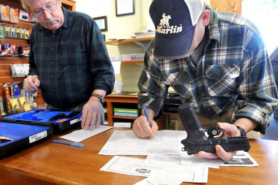 Co-owners Brian Owens, left, and Mike Higgins do the paperwork on the sale of a FNX-45 semi-automatic pistol Thursday at the TGS Outdoors shop in Branford. Mara Lavitt/Register