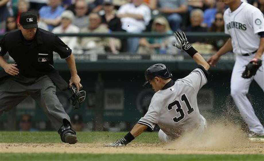 New York Yankees' Ichiro Suzuki (31) scores the winning run against the Seattle Mariners in the ninth inning of a baseball game as home plate umpire Mike Muchlinski watches at left, Sunday, June 9, 2013, in Seattle. (AP Photo/Ted S. Warren) Photo: AP / AP