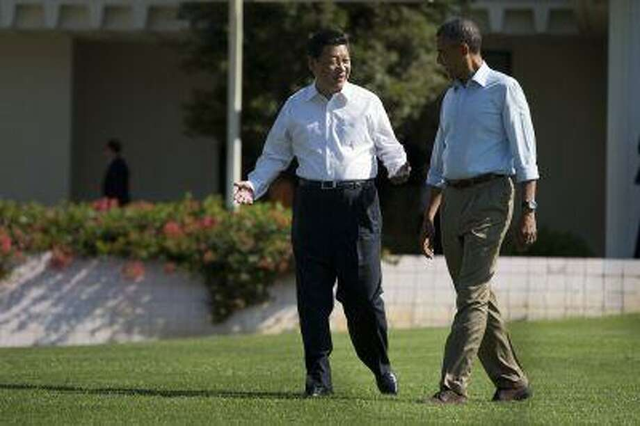 President Barack Obama and Chinese President Xi Jinping, left, walk at the Annenberg Retreat of the Sunnylands estate Saturday, June 8, 2013, in Rancho Mirage, Calif. Photo: AP / AP
