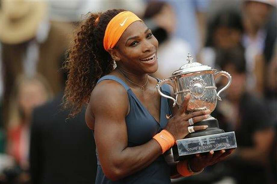 Serena Williams of the U.S. holds the trophy after defeating Russia's Maria Sharapova in two sets 6-4, 6-4, in the women's final of the French Open tennis tournament, at Roland Garros stadium in Paris, Saturday June 8, 2013. (AP Photo/Christophe Ena) Photo: AP / AP