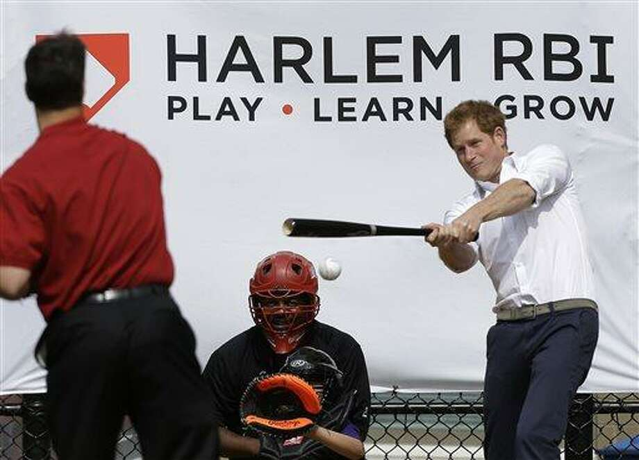 Britain's Prince Harry hits a ball pitched to him by New York Yankees first baseman Mark Teixeira, left, during a visit to Harlem RBI's baseball program in New York, Tuesday, May 14, 2013, to launch a partnership between the organization, the Royal Foundation of the Duke and Duchess of Cambridge, and Prince Harry.  (AP Photo/Kathy Willens) Photo: AP / AP