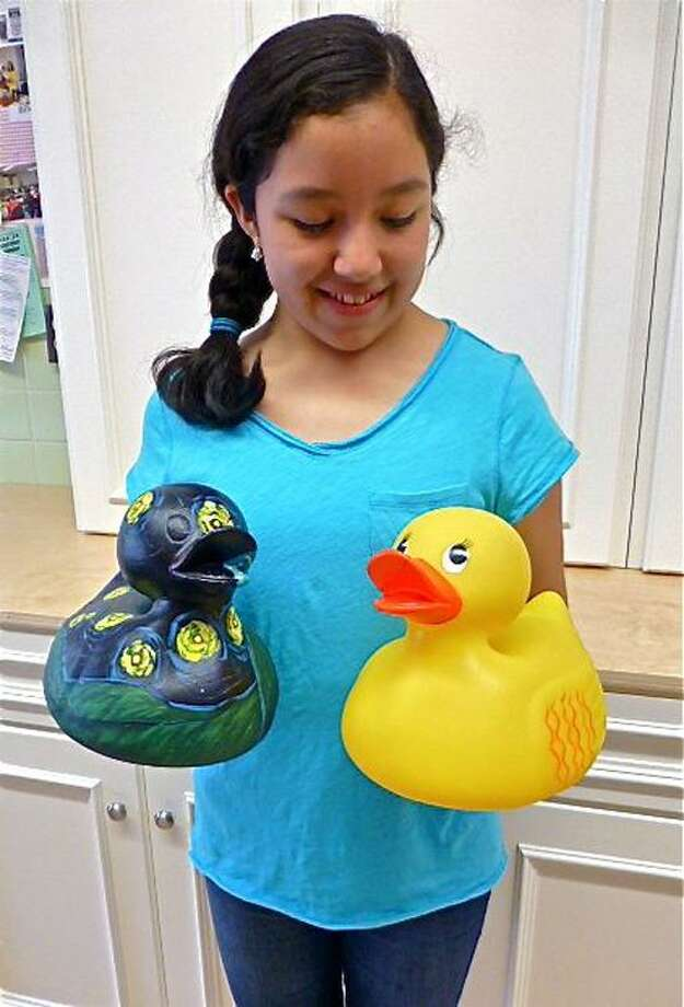 Makayla Naranjo, 12, a sixth-grader at St. Mary-St. Michael School in Derby, shows off two of the decorated rubber ducks from a previous year's contest. Patricia Villers/Register