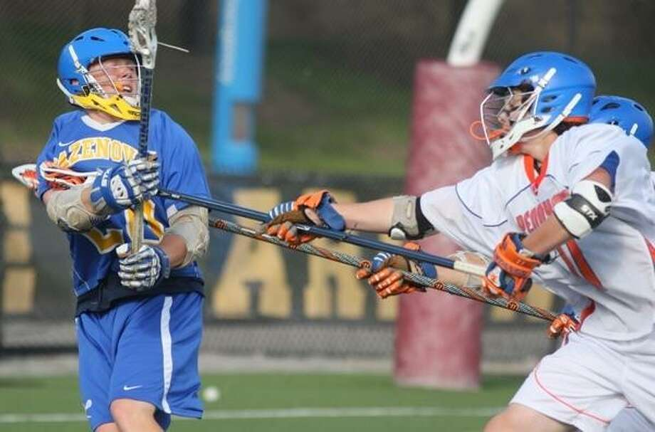 JOHN HAEGER @ONEIDAPHOTO ON TWITTER/ONEIDA DAILY DISPATCH Cazenovia Nate Christensen (20) looks to pass as Penn Yan Academy players  defends in the first half of the Class C NYSPHSAA West Semi-Finals in Rochester on Wednesday, June 6, 2013.