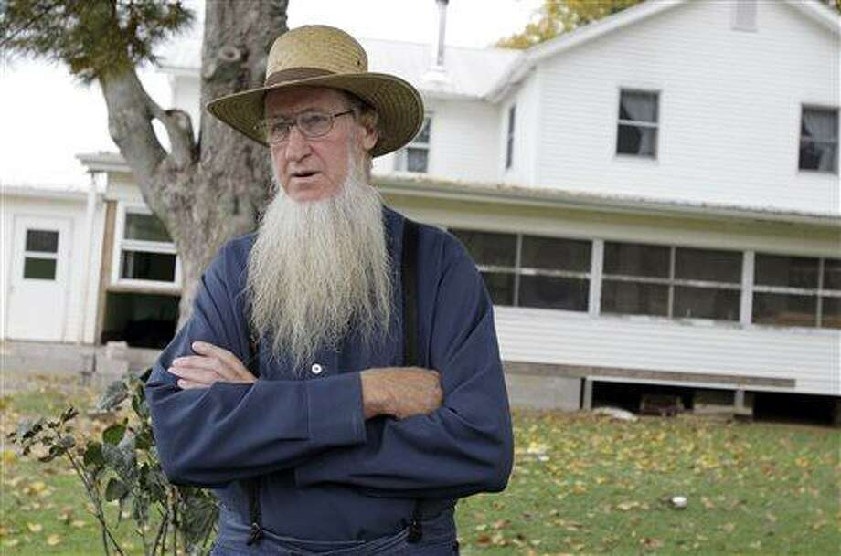 FILE - In this Monday, Oct. 10, 2011 file photo, Sam Mullet stands in front of his Bergholz, Ohio, home. Attorneys for a group of Amish men and women found guilty of hate crimes for cutting the hair and beards of fellow members of their faith in eastern Ohio are arguing that the group's conviction, sentencing and imprisonment in separate facilities across the country violates their constitutional rights and amounts to cruel and unusual punishment, according to recent court filings. The Amish group's leader, Mullet, was sentenced to 15 years in prison, while the rest of the group got sentences ranging from one to seven years. (AP Photo/Amy Sancetta, File) Photo: AP / AP