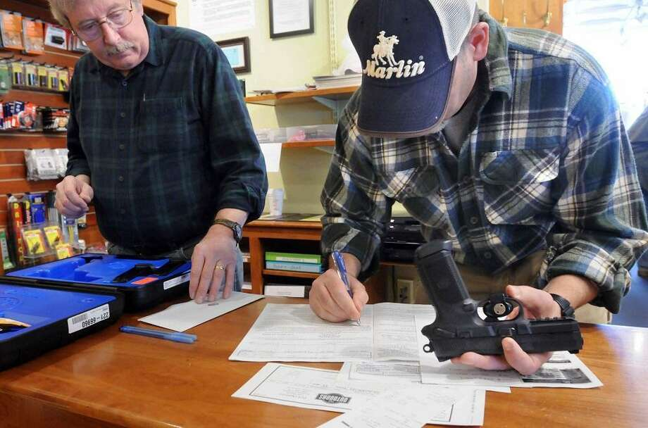 At the TGS Outdoors shop in Branford. Co-owners Brian Owens left and Mike Higgins do the paperwork on the sale of a FNX-45 semi-automatic pistol. Gov. Dan Malloy signed a sweeping gun-control bill into law. Mara Lavitt/New Haven Register 4/4/13