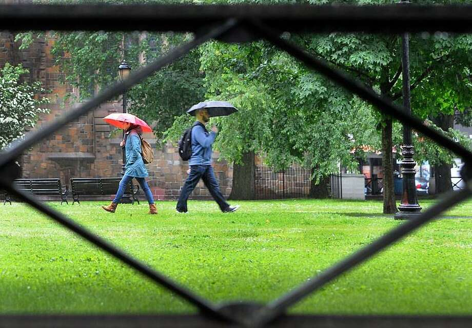 Two people protect themselves from the rain with umbrellas as they walk past each other framed by the iron fence on the upper green in New Haven Friday June 7, 2013. Photo by Peter Hvizdak / New Haven Register Photo: New Haven Register / ©Peter Hvizdak /  New Haven Register