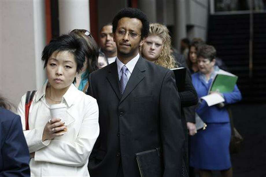 In this Tuesday, April 27, 2010, photo, Job-seekers, including Sophonias Gizaw, center, of Seattle, wait in line to attend a job fair, in Tacoma, Wash. The Labor Department reports on the number of Americans who applied for unemployment benefits for the first full week of May on Thursday, May 9, 2013. (AP Photo/Ted S. Warren) Photo: AP / AP