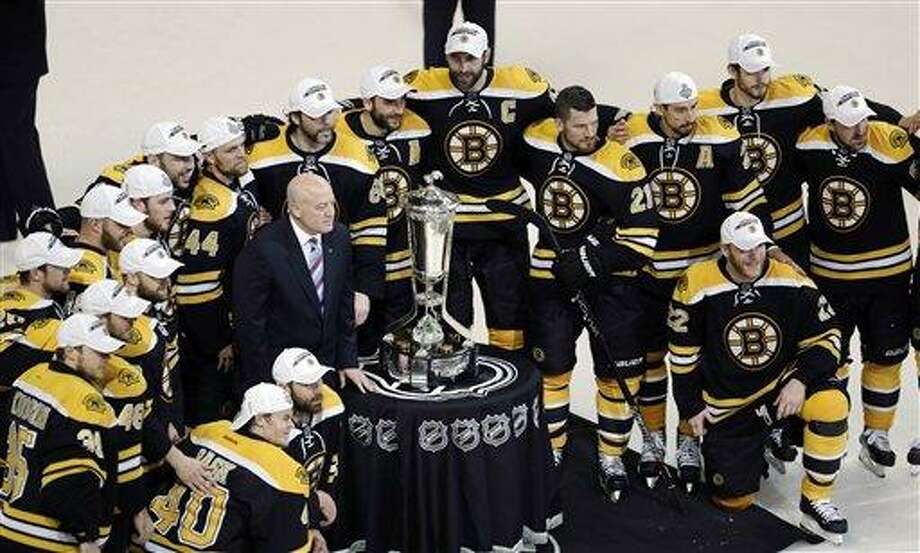 The Boston Bruins pose with the trophy after beating the Pittsburgh Penguins 1-0 in Game 4 of the Eastern Conference finals of the NHL hockey Stanley Cup playoffs in Boston, Friday, June 7, 2013. The Bruins advanced to the Stanley Cup finals.  (AP Photo/Charles Krupa) Photo: AP / AP