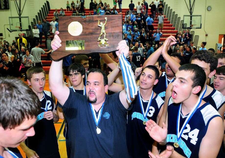 Oxford coach Jeff Giovacchino raises the Class M championship plaque as his team celebrates their victory over Enfield Friday at Shelton High. Photo by Arnold Gold/New Haven Register