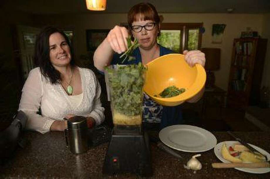 Self-proclaimed weed nerds Erin Smith, left, and Wendy Petty, right, make pesto using a variety of wild greens picked from the garden, including mallow, lamb's-quarters (or wild spinach) and lemon balm. Recipes 3C (Helen H. Richardson/The Denver Post) Photo: DP / Copyright - 2013 The Denver Post, MediaNews Group.