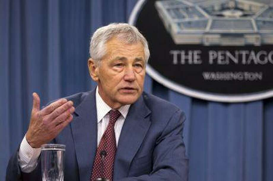 Defense Secretary Chuck Hagel gestures while speaking during a news conference at the Pentagon, Thursday, March 28, 2013. The Pentagon says it's easing the impact of automatic budget cuts on as many as 800,000 civilian employees, sharply reducing the number of unpaid furlough days they will have to take in coming months. Hagel said Thursday a new spending law lets the military services cut furlough days from 22 to 14. (AP Photo/Jacquelyn Martin) Photo: AP / AP