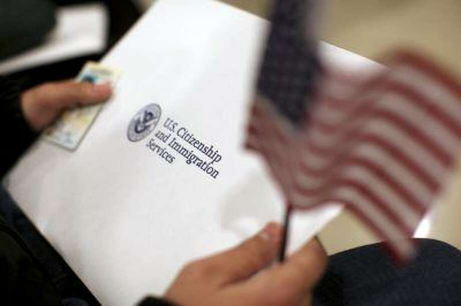 A man holds a U.S. flag while receiving his proof of U.S. citizenship during a ceremony in San Francisco, California January 30, 2013. President Barack Obama said on Wednesday that he believes it is possible to get an overhaul of the U.S. immigration system certainly by the end of the year if not the first half of 2013. REUTERS/Robert Galbraith (UNITED STATES - Tags: POLITICS SOCIETY IMMIGRATION) Photo: REUTERS / X90034