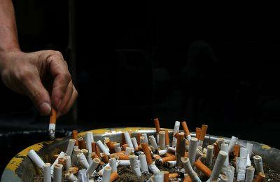 A man discards a cigarette butt outside a construction site. Photo: REUTERS / X01865