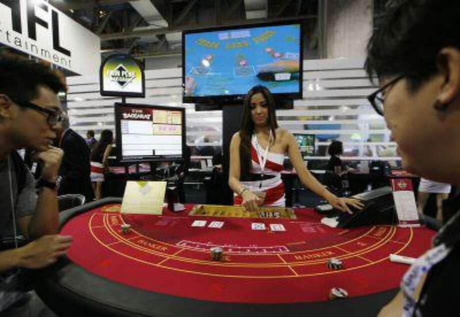 In this photo taken on Thursday, May 23, 2013, an attendant demonstrates the game of baccarat on a baccarat gaming table during the Global Gaming Expo Asia in Macau. Photo: AP / AP