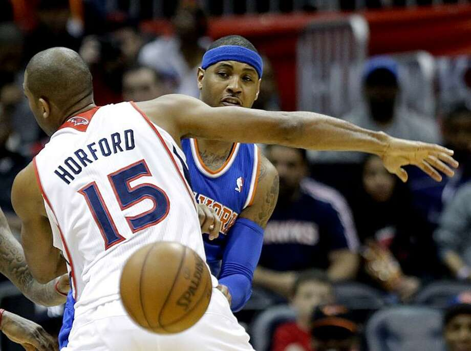 New York Knicks' Carmelo Anthony, right, passes the ball behind the back of Atlanta Hawks' Al Horford in the second quarter of an NBA basketball game, Wednesday, April 3, 2013, in Atlanta. (AP Photo/David Goldman) Photo: AP / AP2013