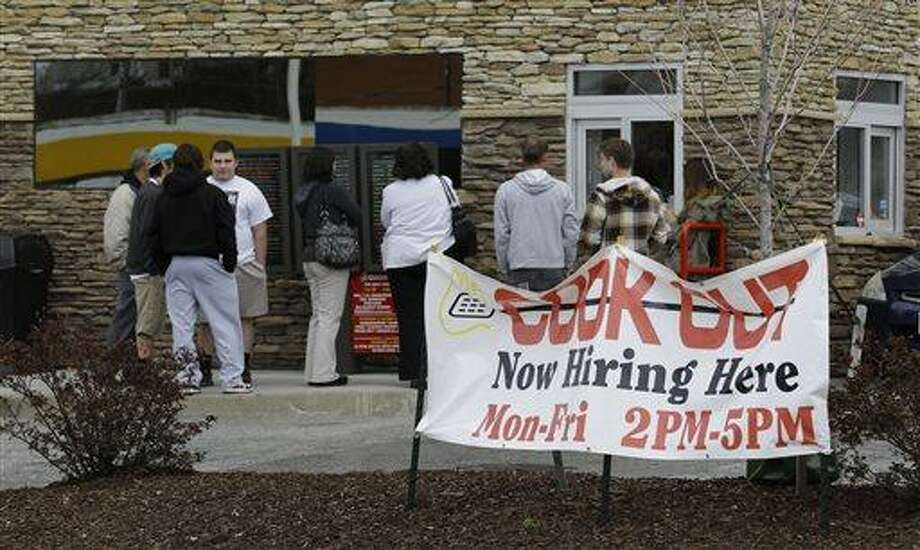 In this Friday, March 29, 2013, people line up outside a restaurant in front of a help wanted sign in Richmond, Va. The number of Americans seeking unemployment aid rose to a four-month high in the week ending March 30, 2013, although the increase partly reflects seasonal distortions around the spring holidays. The Labor Department says weekly applications increased 28,000 to a seasonally adjusted 385,000. That is the highest level since late November. The four-week average, a less volatile measure, rose to 354,250.  (AP Photo/Steve Helber) Photo: AP / AP