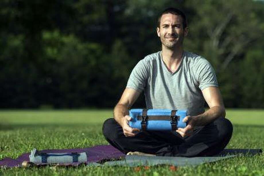 Ryon Lane wanted to run to yoga class, but a rolled-up mat flopping around for three miles wasn't what he pictured, so he developed the YogoMat, which folds up to fit in a backpack. (Washington Post/Bonnie Jo Mount) Photo: THE WASHINGTON POST / THE WASHINGTON POST
