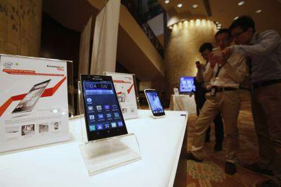 Lenovo smartphones are displayed during a news conference on the company's annual results in Hong Kong May 23, 2013. Lenovo Group Ltd's bold acquisitions in its flagship PC business, a foray into mobile gadgets, and a relatively light debt load are setting it apart from PC rivals as industry shipments take their steepest fall in decades. Photo: REUTERS / X00306