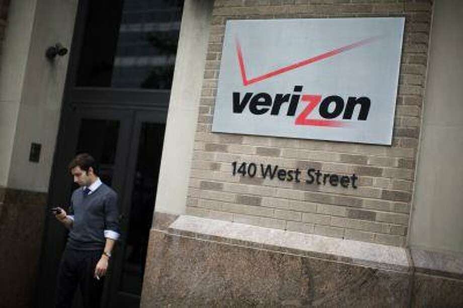 A man checks his cell phone during a smoke break outside the Verizon headquarters in lower Manhattan, Thursday, June 6, 2013, in New York. The government has been secretly collecting the telephone records of millions of U.S. customers of Verizon under a top secret court order according to Sen. Diane Feinstein, D-Calif., the chairwoman of the Senate Intelligence Committee. (AP Photo/John Minchillo) Photo: AP / FR170537 AP