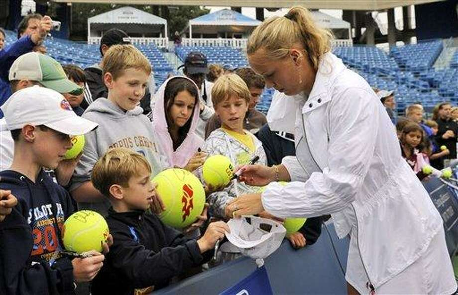 Denamrk's Caroline Woznacki signs autographs for young fans after she defeated Russia's Elena Visnina 6-2, 6-4 in the finals at the Pilot Pen tennis tournament in New Haven, Conn., Saturday, Aug. 29, 2009.  (AP Photo/Bob Child) Photo: AP / FR170410 AP