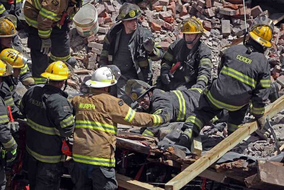 A  Philadelphia Firefighter, center, lays with his hand thrust into an empty area underneath a clothing rack under the rubble of a collapsed building on the edge of downtown Philadelphia, Wednesday, June 5, 2013. A building that was being torn down collapsed with a thunderous boom, raining bricks on a neighboring thrift store, killing six people and injuring at least 13 others in an accident that witnesses said was bound to happen. Rescue crews were trying to extricate one person still trapped amid the rubble inside the Salvation Army thrift store, which was nearly obliterated by falling debris. (AP Photo/The Philadelphia Inquirer, Michael Bryant) Photo: ASSOCIATED PRESS / AP2013