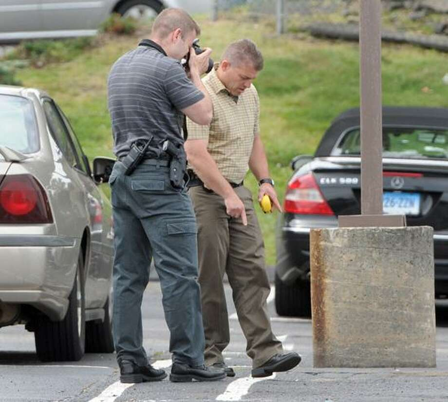 "Milford Police investigate a complaint of shots being discharged in the parking lot of Howard Johnson Hotel in Milford, Connecticut Thursday, June 6, 2013.  ""A preliminary investigation revealed that there was a dispute between two parties in the parking lot which led to the discharging of a firearm,"" according to a police press release. Photo by Peter Hvizdak / New Haven Register Photo: New Haven Register / ©Peter Hvizdak /  New Haven Register"