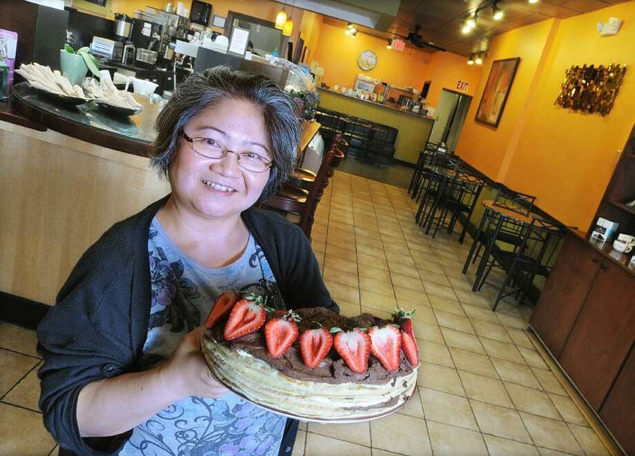 "Catherine Avalone/The Middletown PressTrang Tran, baker and manager of Sweet Harmony Cafe & Bakery shows off her Tuxedo Chocolate Moose Crepe Cake with fresh strawberries at their new location at 	330 Main Street in Middletown, formerly Javapalooza. Sweet Harmony moved from Broad Street and will continue to serve coffees and menu items from Javapalooza. ""Sweet Harmony offers fresh made crepes made to order and breakfast all day. Gourmet cake to order, you dream it, we can make it."" said Tran. Hours are Monday through Friday 6 a.m.-5 p.m. Friday and Saturday 6 a.m. - 7 p.m. and Sunday 7 a.m. - 5 p.m. Visit their website at www.sweetharmonycafebakery.com / TheMiddletownPress"