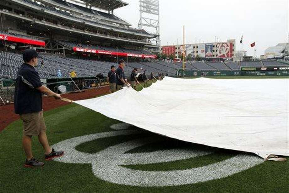 The grounds crew covers the field before a baseball game between the Washington Nationals and the New York Mets at Nationals Park Thursday, June 6, 2013, in Washington. (AP Photo/Alex Brandon) Photo: AP / AP
