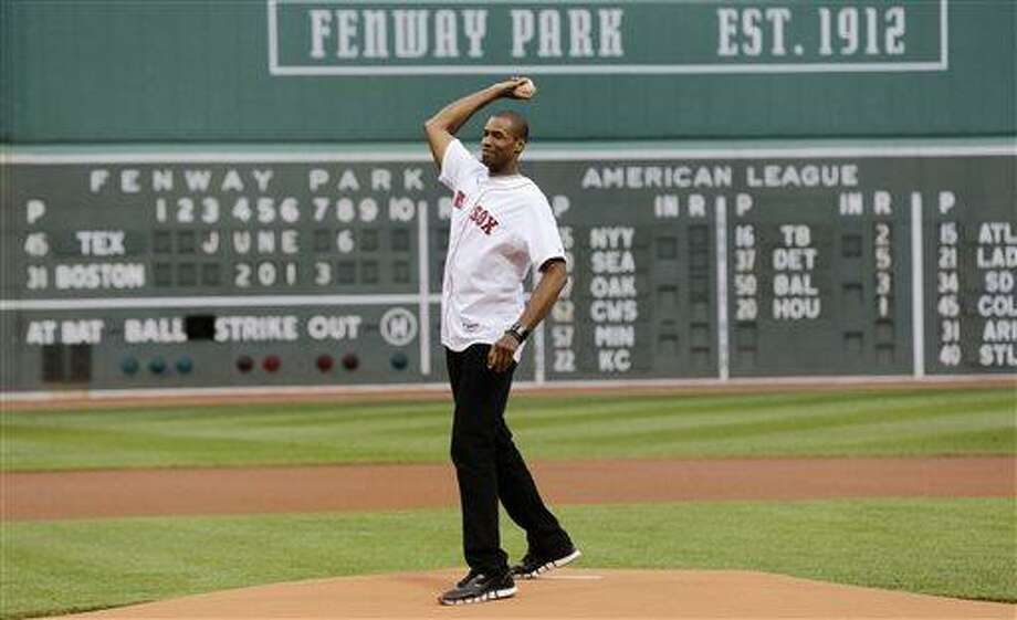 Jason Collins, the first active athlete to come out as being gay in one of the four U.S. major professional sports leagues, throws out a ceremonial first pitch at Fenway Park before a baseball game between the Boston Red Sox and the Texas Rangers in Boston, Thursday, June 6, 2013. Collins played for six NBA teams in 12 seasons. He was dealt in a midseason trade from the Boston Celtics to the Washington Wizards and becomes a free agent July 1. (AP Photo/Charles Krupa) Photo: AP / AP