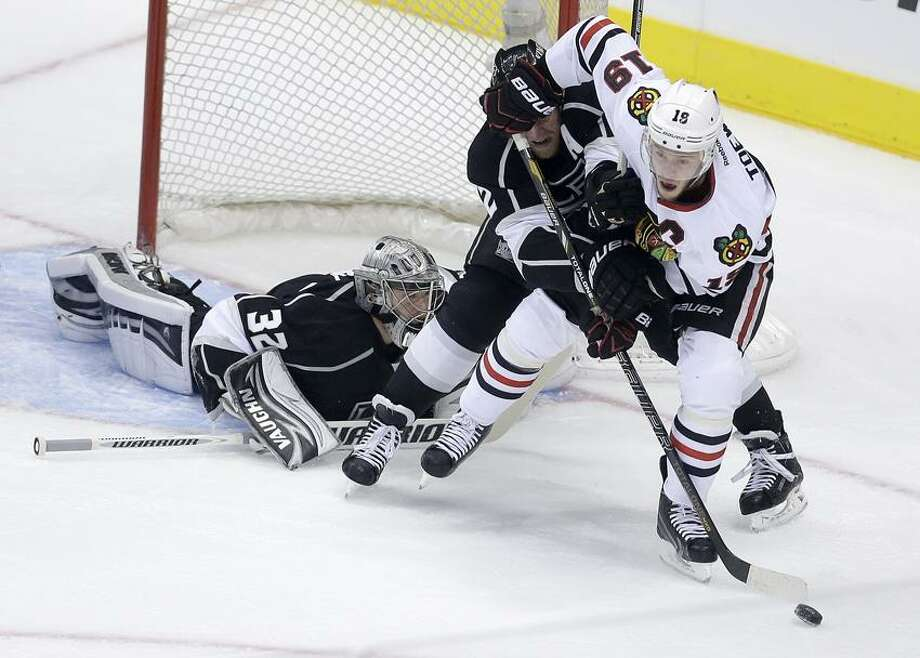 Chicago Blackhawks center Jonathan Toews, right, works the puck against Los Angeles Kings defenseman Matt Greene, middle, and goalie Jonathan Quick during the first period in Game 4 of the NHL hockey Stanley Cup playoffs Western Conference finals, in Los Angeles on Thursday, June 6, 2013. (AP Photo/Chris Carlson) Photo: AP / AP