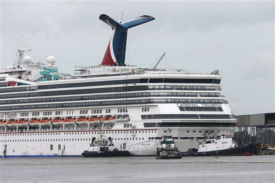 Tug boats maneuver around the Carnival cruise ship Triumph as it rests against a dock on the east side of the Mobile River after becoming dislodged from its mooring at BAE Shipyard during high winds Wednesday, April 3, 2013 in Mobile, Ala. Triumph was disabled Feb. 10 by an engine fire that stranded thousands of passengers onboard for days in the Gulf. It was towed into port in Mobile. (AP Photo/AL.com, Bill Starling)  MAGS OUT Photo: AP / AL.com