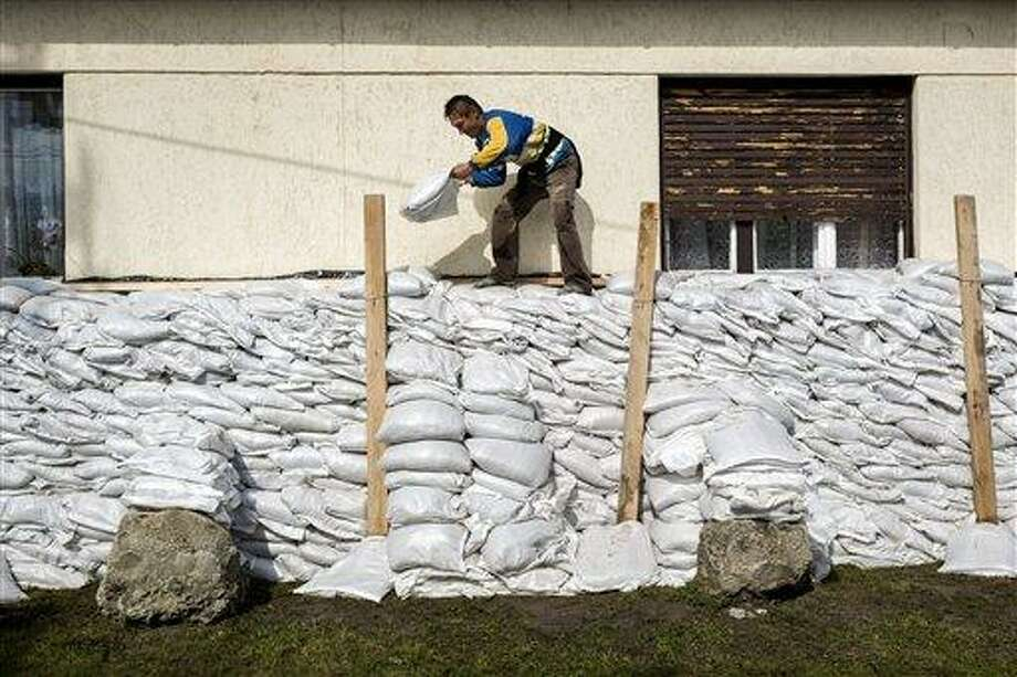 Local man protects his house with sandbags in Tahitotfalu some 30 kms north of Budapest, Hungary, Wednesday, June 5, 2013 as the prevention works continue in the region against the flooding River Danube.  (AP Photo/MTI,Balazs Mohai) Photo: AP / MTI