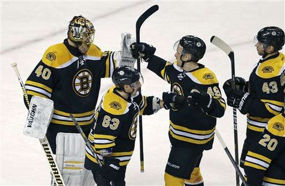 Boston Bruins goalie Tuukka Rask (40) is congratulated by teammates after shutting out the New Jersey Devils 1-0 in an NHL hockey game in Boston, Thursday, April 4, 2013. (AP Photo/Charles Krupa) Photo: ASSOCIATED PRESS / AP2013