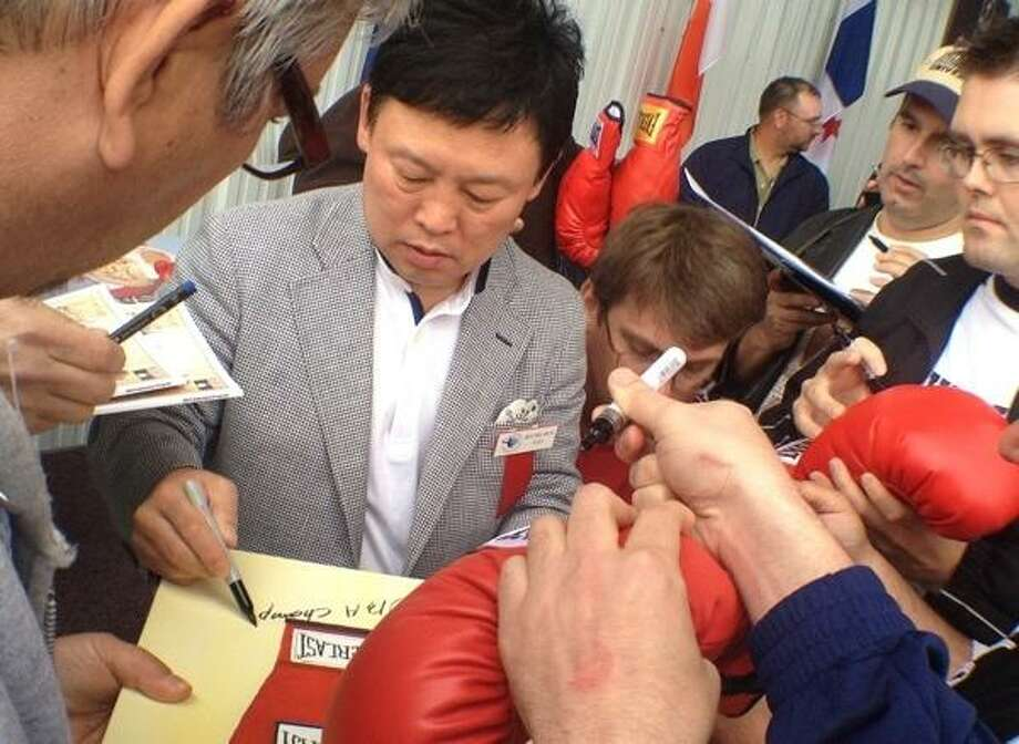 JOHN HAEGER @ONEIDAPHOTO ON TWITTER/ONEIDA DAILY DISPATCH Class of 2013 Hall of Fame Inductee Myung-Woo Yuh signs autographs for fans at the International Boxing Hall of Fame in Canastota on Thursday, June 6, 2013.