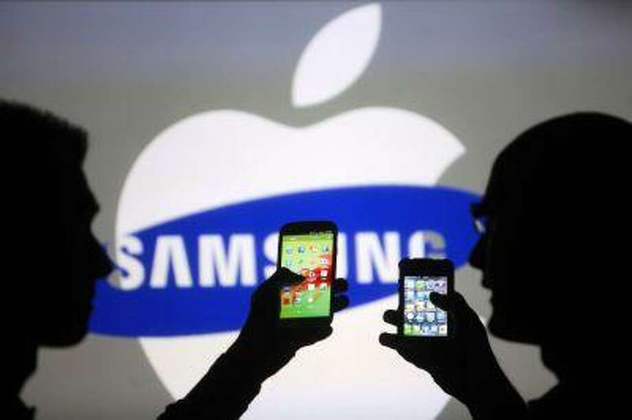 Men are silhouetted against a video screen as they pose with Samsung Galaxy S3 and iPhone 4 smartphones in this photo illustration taken in the central Bosnian town of Zenica, May 17, 2013. Photo: REUTERS / X02714