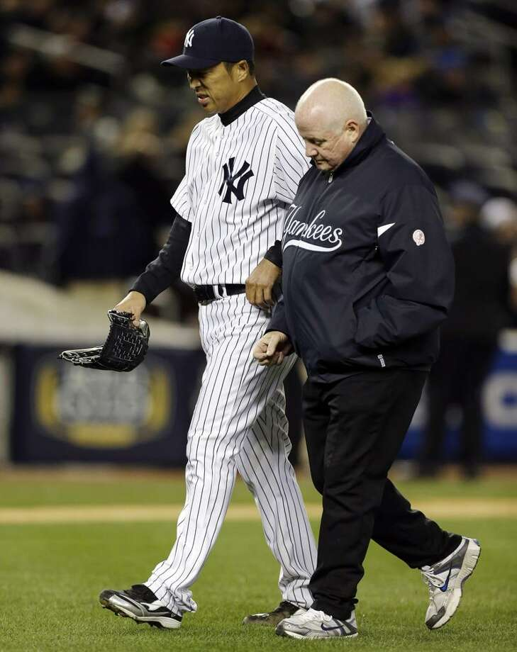 New York Yankees starting pitcher Hiroki Kuroda leaves the mound with head athletic trainer Steve Donohue during the second inning of a baseball game against the Boston Red Sox at Yankee Stadium in New York, Wednesday, April 3, 2013. (AP Photo/Kathy Willens) Photo: AP / AP2013