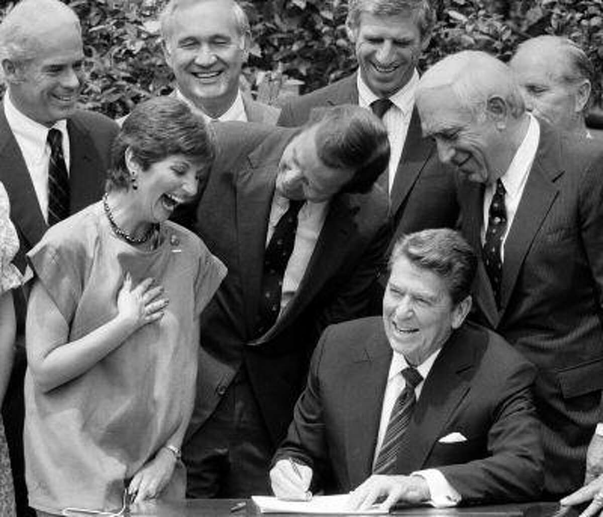 CORRECTS LAUTENBERG'S PARTY AFFILIATION IN FIRST SENTENCE TO DEMOCRAT, INSTEAD OF REPUBLICAN - FILE - In this July 17, 1984 file photo, President Ronald Reagan, seated, signs legislation raising the national drinking age to 21 while New Jersey Democrat Sen. Frank Lautenberg, center right, New Jersey Gov. Thomas Kean, center and MADD founder Candy Lightner, center left, look on. Lautenberg, a multimillionaire New Jersey businessman who New Jersey Democrats recruited out of retirement in September 2002, has died at age 89. In addition, from left, back, are Rep. John Edward Porter, R-Ill.; Rep. Gene Snyder, R-Ky. and Sen. John Danforth, R-Mo. (AP Photo, File)
