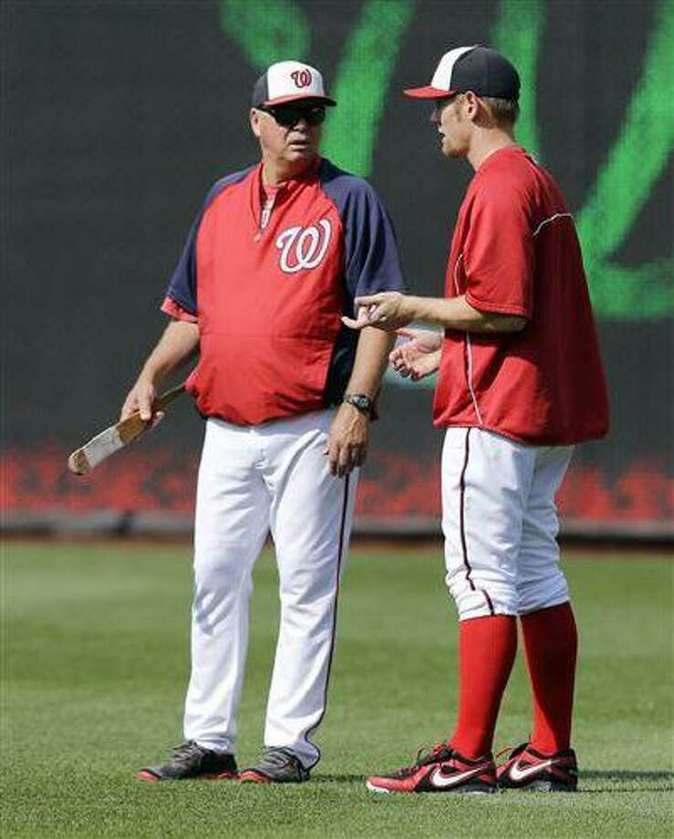 Washington Nationals pitching coach Steve McCatty, left, talks with starting pitcher Stephen Strasburg before a game against the New York Mets at Nationals Park Wednesday in Washington. Strasburg has been placed on the disabled list. Photo: AP / AP