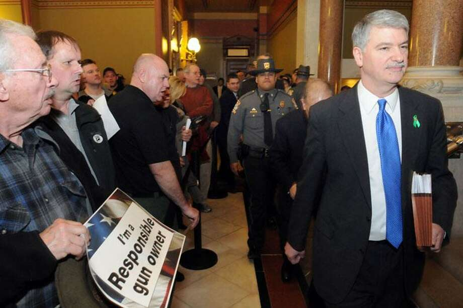 State Capitol, Hartford: pro-gun protestors fill the State Capitol prior to legislators debating a sweeping gun control bill. Sen. Pro Tempore Donald Williams and Sen. Martin Looney behind him go through the yelling crowd under police guard. Mara Lavitt/New Haven Register4/3/13