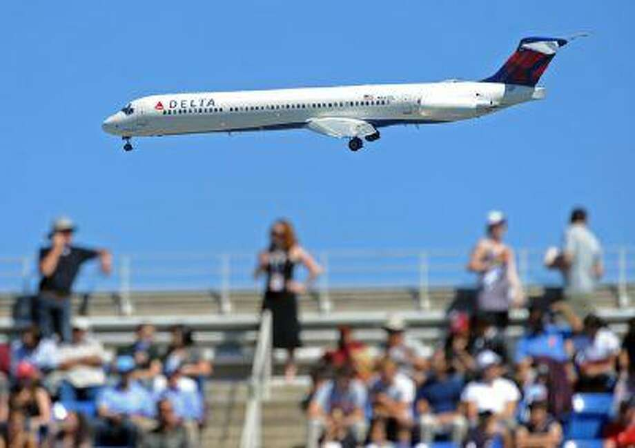 A Delta Air Lines Inc. jet makes its approach to nearby LaGuardia Airport past the Arthur Ashe Stadium during the U.S. Open tennis semifinals in New York. (Stan Honda/AFP via Getty Images)