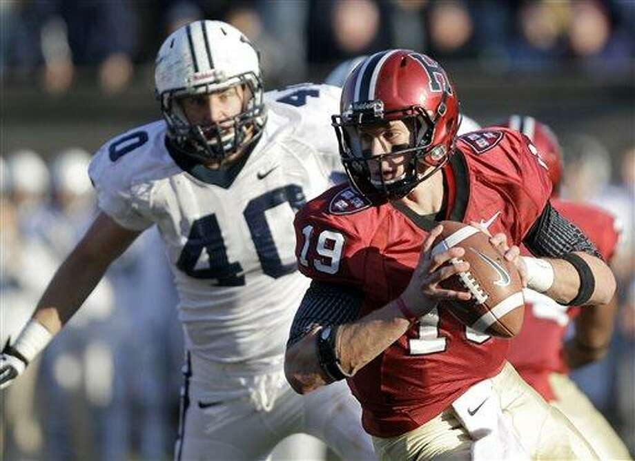 Harvard quarterback Colton Chapple (19) rushes with the ball ahead of Yale defensive end Beau Palin (40) during the second half of their NCAA college football game in Cambridge, Mass., Saturday, Nov. 17, 2012. (AP Photo/Mary Schwalm) Photo: AP / FR158029 AP
