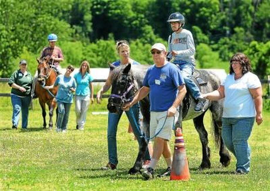 """Catherine Avalone/The Middletown Press Kevin Ajodhi, a student at Wethersfield Transitional Academy learns first time riding skills and verbal communications at Manes & Motions Therapeutic Riding Center on Millbrook Road in Middletown. Kris Hawkins leads Oreo and sidewalkers Jeanine Berasi, left and Kristen Millard, right during a class Wednesday afternoon. """"We have plans to build an indoor riding arena with classrooms to allow a year-round program regardless of the weather,"""" said Janice Anderson, the Facility Coordinator. / TheMiddletownPress"""