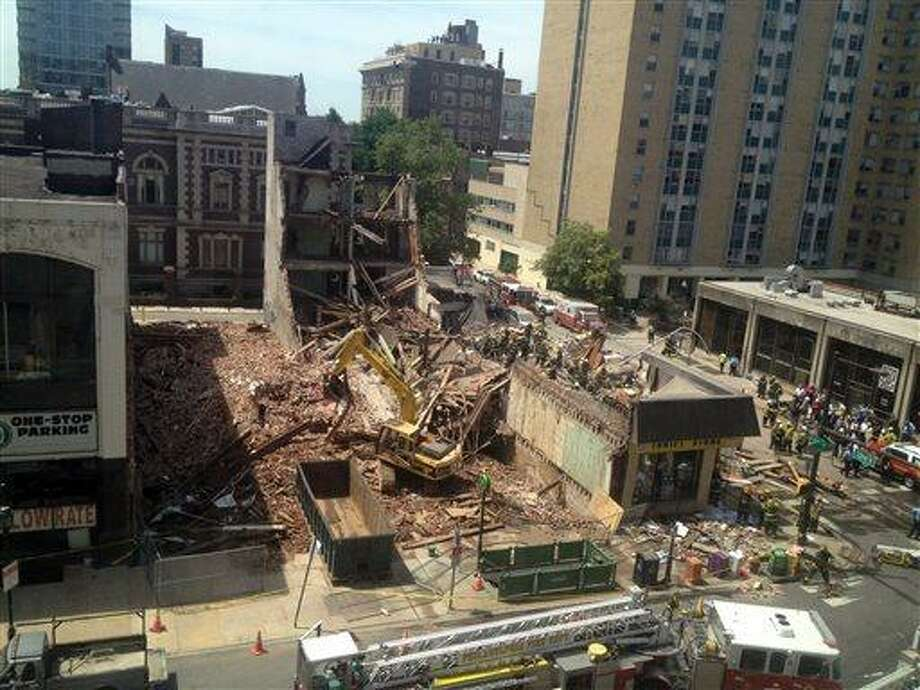 Emergency personnel respond to a building collapse in downtown Philadelphia, where the city fire commissioner says as many as eight to 10 people are believed trapped in the rubble, Wednesday, June 5, 2013. (AP Photo/Dino Hazell) Photo: AP / AP