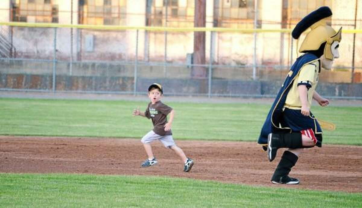 Titus and a lucky fan race around the bases in between innings. John Berry/Register Citizen.